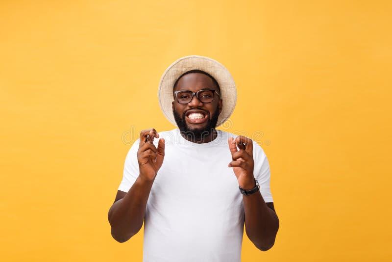 Il giovane uomo afroamericano sopra le dita d'attraversamento sorridenti isolate del fondo con speranza e gli occhi si è chiuso F immagini stock libere da diritti