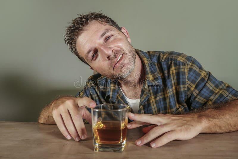 Il giovane uomo alcolico ubriaco ed orinato ha sprecato inebriata di vetro bevente del whiskey e sudicio su fondo scuro in alcool immagini stock libere da diritti