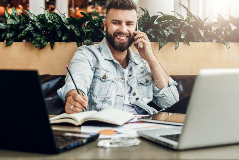 Il giovane uomo allegro barbuto si siede alla tavola davanti ai computer portatili, parlanti sul telefono cellulare mentre fa le  fotografie stock libere da diritti