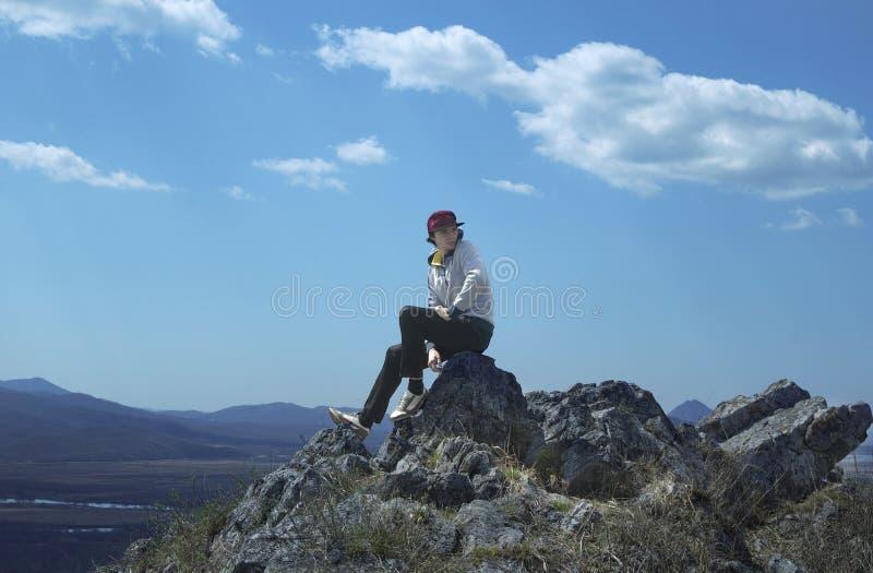 Il giovane uomo allegro in spiritello malevolo si siede fotografia stock