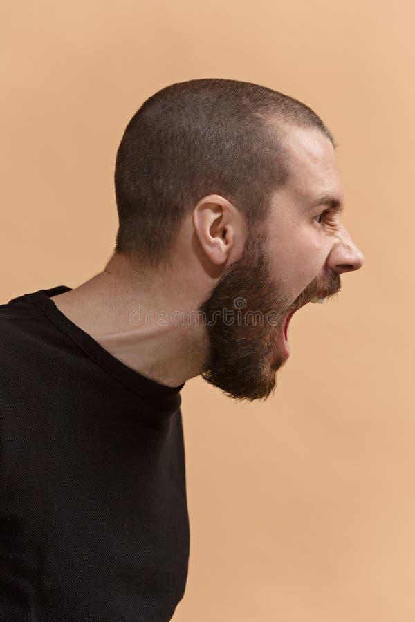 Il giovane uomo arrabbiato emozionale che grida sul fondo pastello dello studio fotografie stock