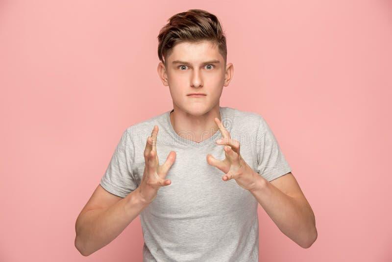 Il giovane uomo arrabbiato emozionale che grida sul fondo rosa dello studio fotografia stock libera da diritti