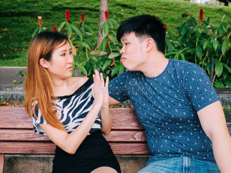 Il giovane uomo asiatico che prova a baciare una ragazza ed ottiene rifiutato immagini stock libere da diritti