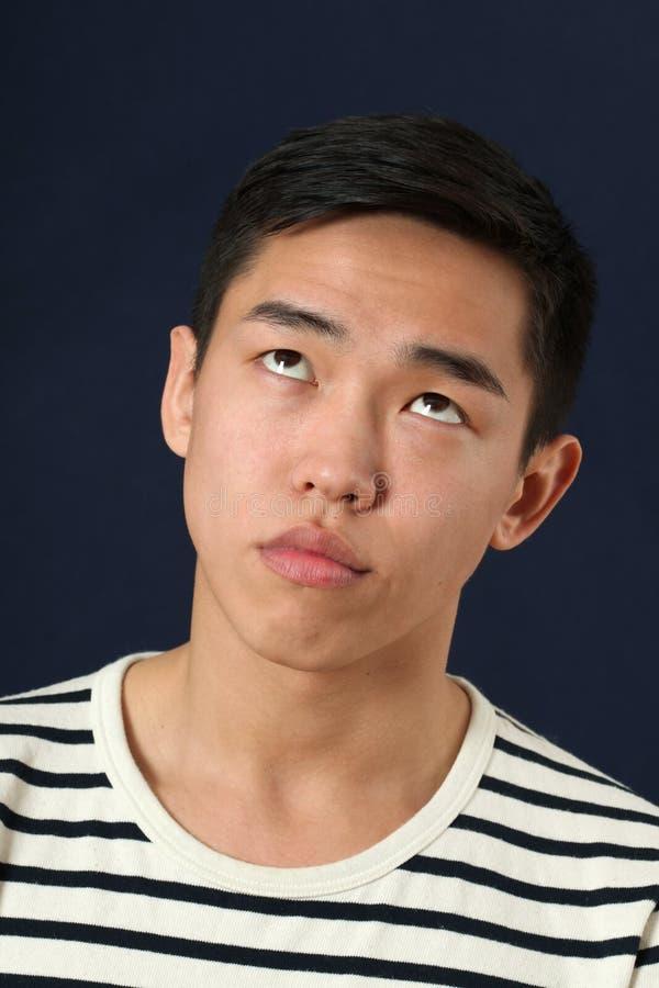 Il giovane uomo asiatico divertente che fa il fronte e che rotola osserva su immagini stock libere da diritti