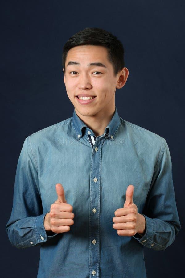 Il giovane uomo asiatico sorridente che dà i pollici aumenta i segni immagini stock