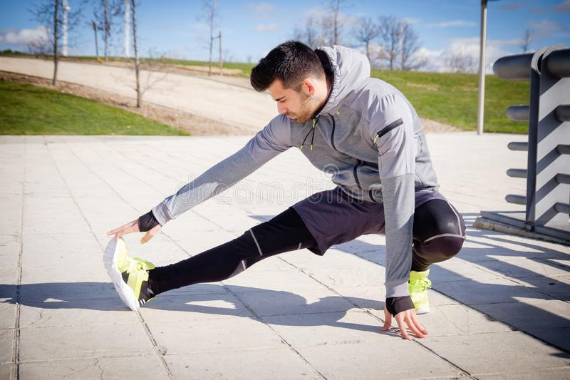 Il giovane uomo atletico sta preparando prima di correre fotografia stock libera da diritti