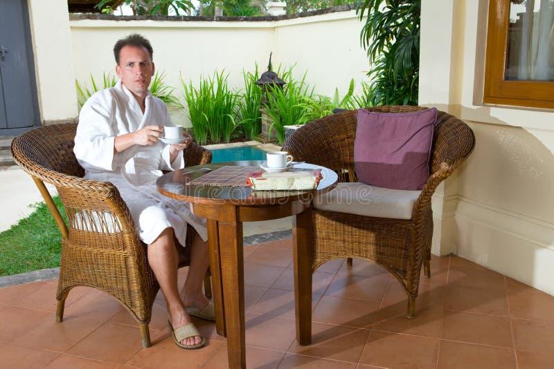 Il giovane uomo attraente beve il tè al raggruppamento su resto fotografia stock