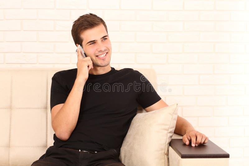 Il giovane uomo attraente in camicia nera sta sedendosi sul sofà e sta parlando sul telefono a casa Copi lo spazio fotografie stock