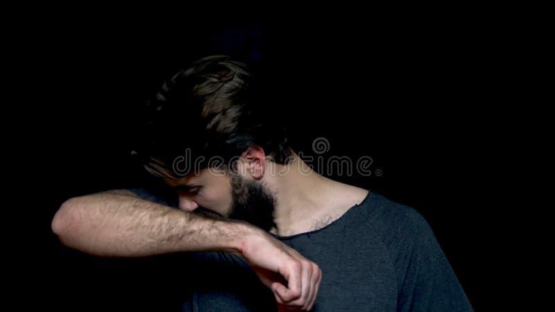 Il giovane uomo barbuto che fiuta la sua ascella, qualcosa puzza molto cattivo, isolato su fondo nero Emozione negativa, facciale fotografia stock