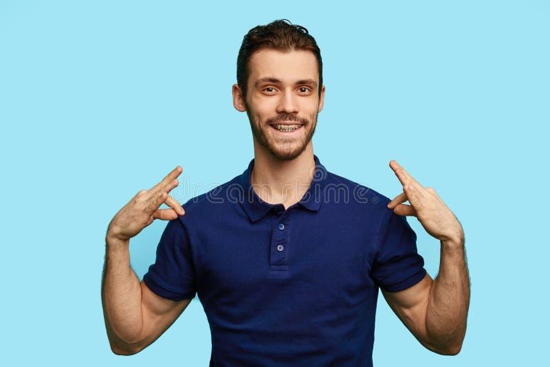 Il giovane uomo bello alla moda è sorridente ed indicante alla sua maglietta blu fotografie stock