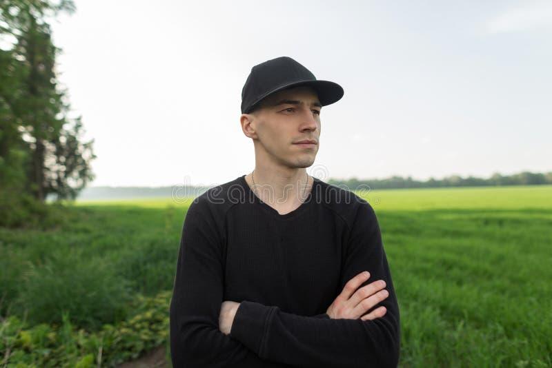 Il giovane uomo bello in berretto nero alla moda in camicia d'annata nera sta in un campo con erba verde all'aperto Il modello pi immagini stock
