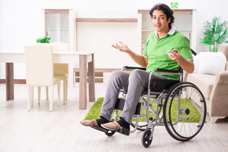 Il giovane uomo bello in sedia a rotelle a casa fotografia stock libera da diritti