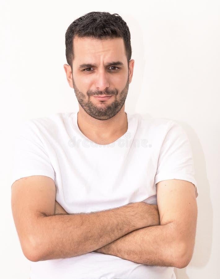 Il giovane uomo caucasico con le sue mani ha attraversato, sembra ferito e triste immagini stock libere da diritti