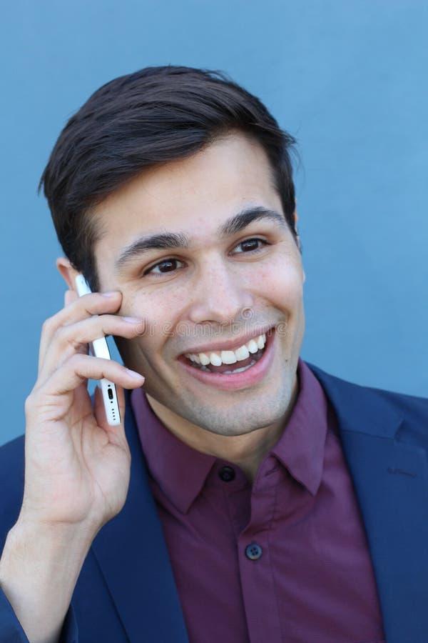 Il giovane uomo d'affari è stato sorpreso ricevere un telefono, isolato su fondo blu fotografia stock libera da diritti