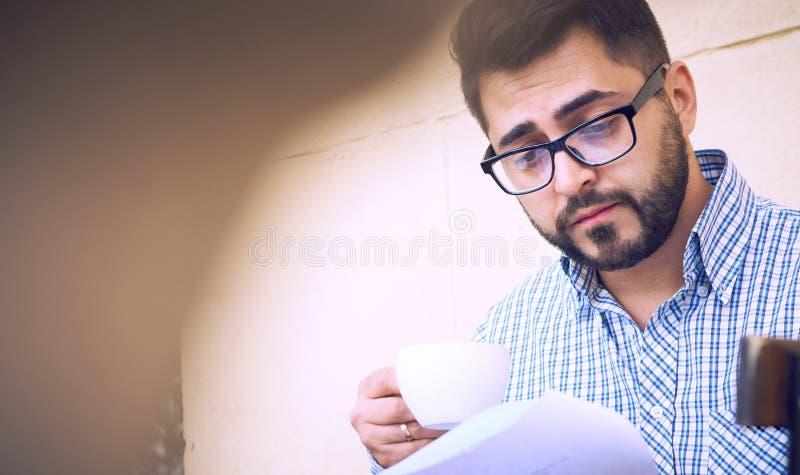 Il giovane uomo d'affari in abbigliamento casual ed occhiali sta studiando il documento mentre beveva il caffè sul terrazzo di un immagini stock libere da diritti