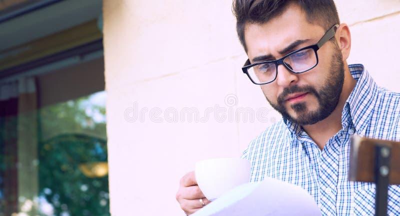 Il giovane uomo d'affari in abbigliamento casual ed occhiali sta studiando il documento mentre beveva il caffè sul terrazzo di un immagine stock libera da diritti