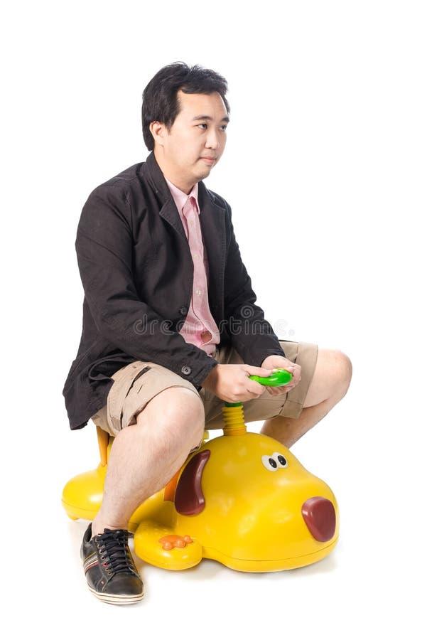 Il giovane uomo d'affari asiatico che determina un assomigliare dell'automobile del giocattolo del bambino al cane, è immagine stock libera da diritti