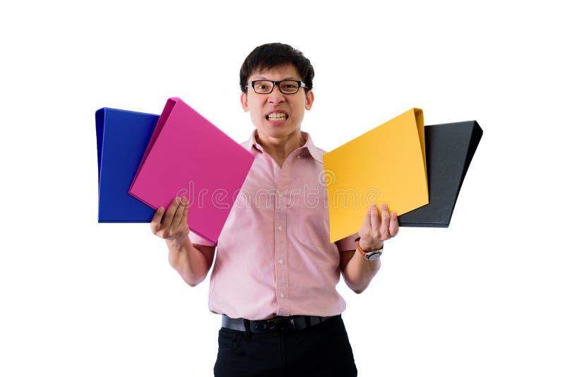 Il giovane uomo d'affari asiatico ha stare e tenuta i molti documenti e cartelle con il ribaltamento sull'isolato su sul fondo de fotografia stock libera da diritti