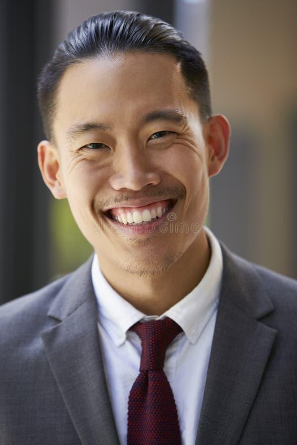 Il giovane uomo d'affari asiatico sorride alla macchina fotografica, fine su, verticale immagine stock libera da diritti