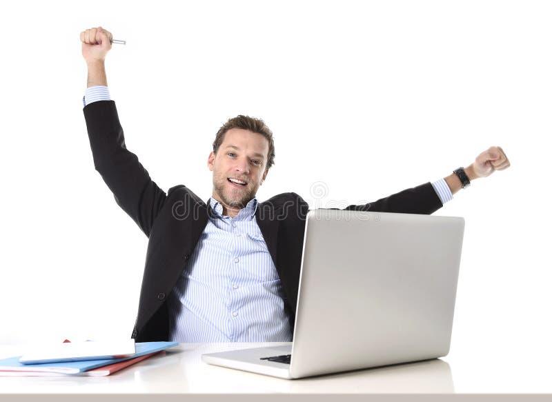 Il giovane uomo d'affari attraente felice ed intenso sul lavoro d'ufficio che si siede allo scrittorio del computer ha soddisfatt immagini stock libere da diritti