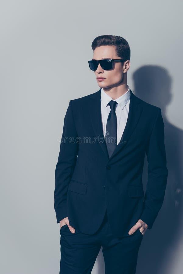 Il giovane uomo d'affari attraente in occhiali da sole ha messo le sue armi nel poc immagine stock libera da diritti