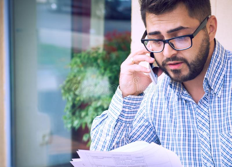 Il giovane uomo d'affari barbuto in abbigliamento casual ed occhiali sta studiando il documento mentre parlava sulla seduta dello fotografia stock libera da diritti