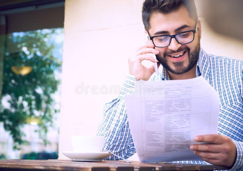 Il giovane uomo d'affari barbuto in abbigliamento casual ed occhiali sta studiando il documento mentre parlava sulla seduta dello fotografia stock