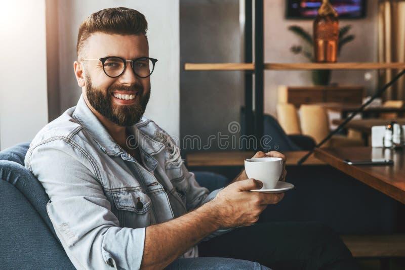 Il giovane uomo d'affari barbuto attraente in vetri d'avanguardia si siede in caffè, beve il caffè durante il tempo del pranzo, r fotografia stock