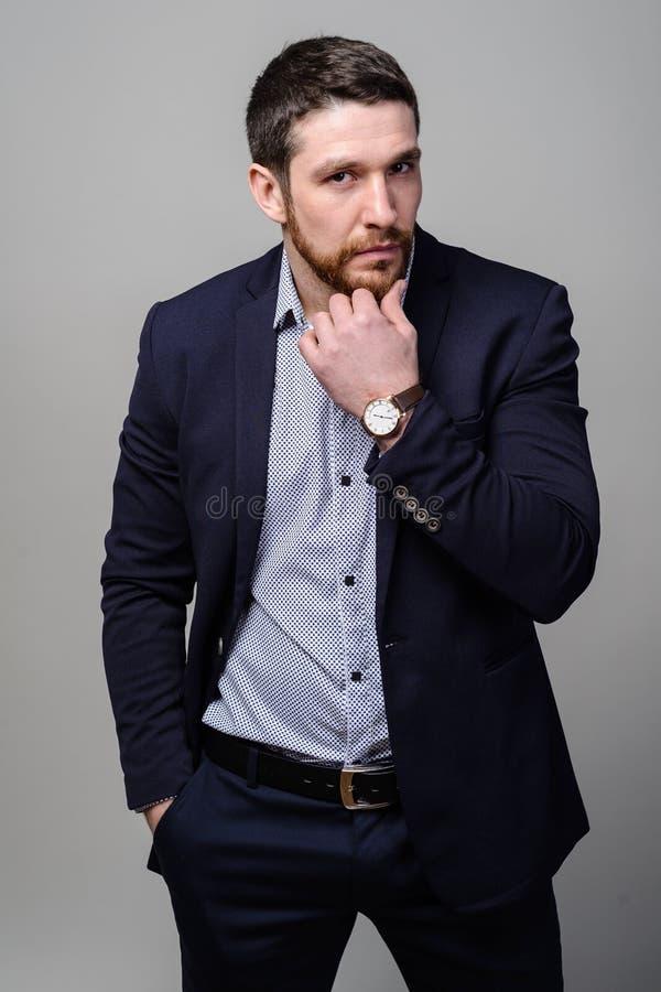 Il giovane uomo d'affari barbuto bello in vestito classico sta regolando il suo rivestimento immagini stock libere da diritti