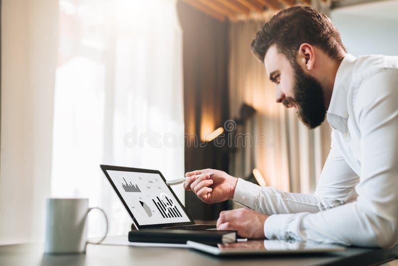 Il giovane uomo d'affari barbuto in camicia bianca sta sedendosi alla tavola davanti al computer, indicante con la penna sui graf immagini stock