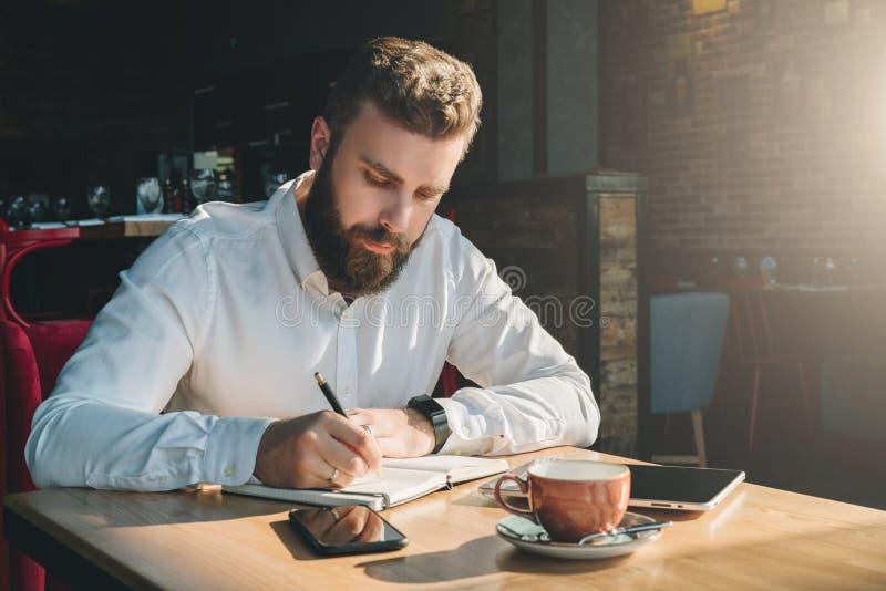 Il giovane uomo d'affari barbuto si siede in caffè, casa alla tavola e scrive in taccuino Sul computer della compressa della tavo immagini stock