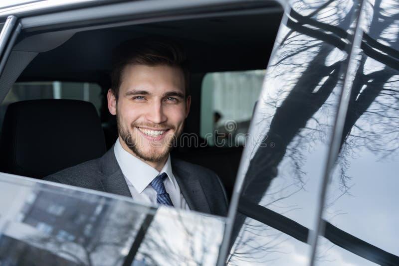 Il giovane uomo d'affari bello sta sedendosi in automobile di lusso fotografia stock libera da diritti