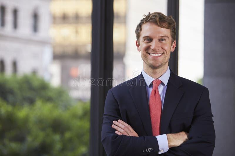 Il giovane uomo d'affari bianco con le armi ha attraversato sorridere, vita su immagini stock