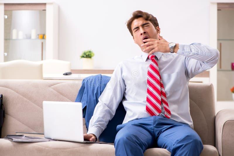 Il giovane uomo d'affari che lavora a casa seduta sul sofà immagine stock