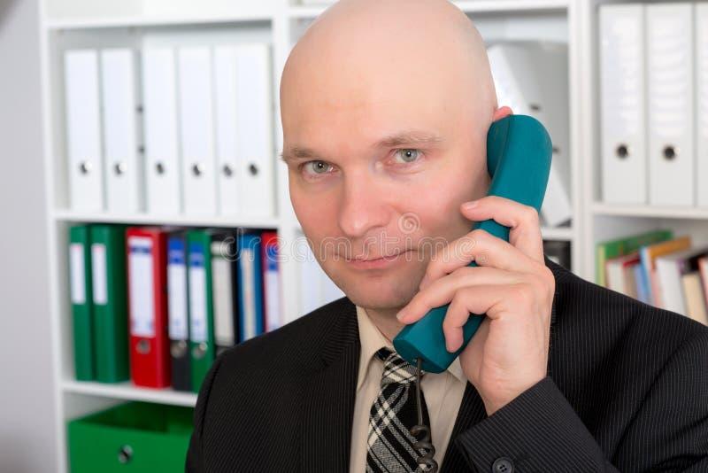 Il giovane uomo d'affari con la testa calva sta chiamando fotografie stock