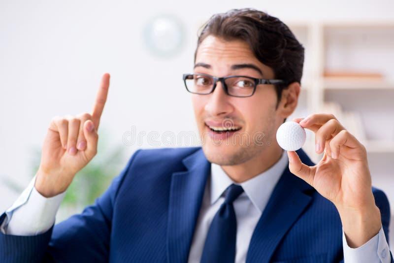 Il giovane uomo d'affari con palla da golf che funziona nell'ufficio fotografia stock libera da diritti