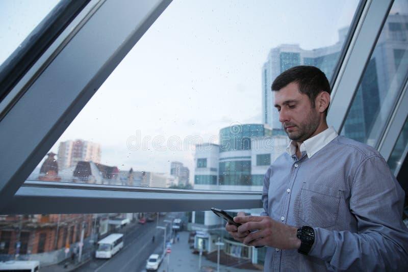 il giovane uomo d'affari con un fronte serio sta passando in rassegna le notizie su un telefono cellulare contro lo sfondo di una fotografia stock