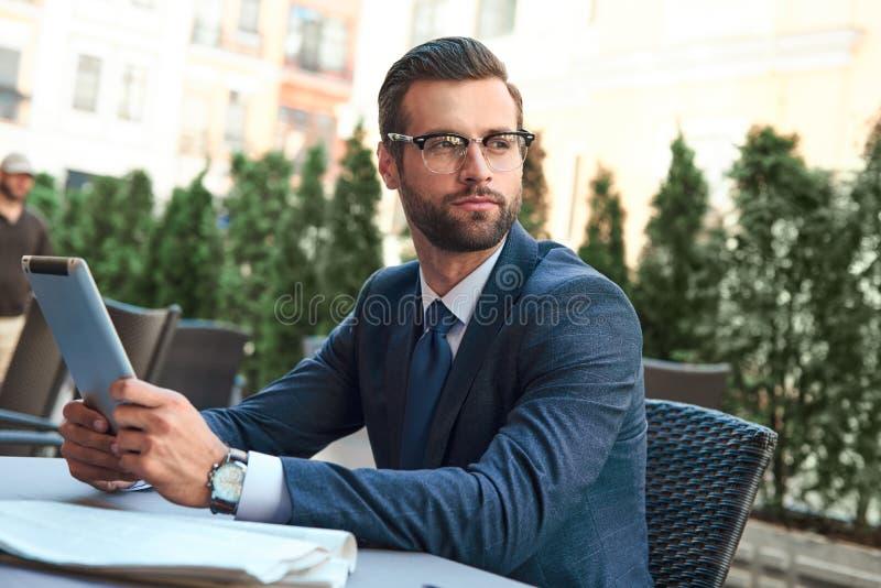 Il giovane uomo d'affari con una barba ed i vetri d'uso è sedentesi ed esaminante la compressa fotografie stock libere da diritti