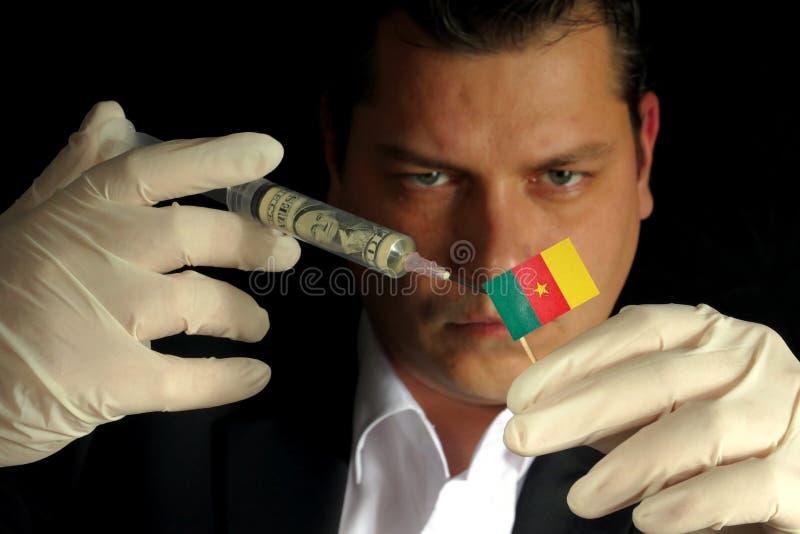 Il giovane uomo d'affari fa un'iniezione finanziaria alla bandiera camerunese immagini stock libere da diritti