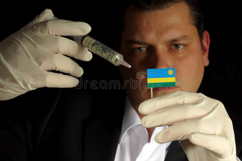 Il giovane uomo d'affari fa un'iniezione finanziaria alla bandiera ruandese è immagini stock
