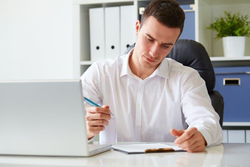 Il giovane uomo d'affari firma un documento fotografia stock
