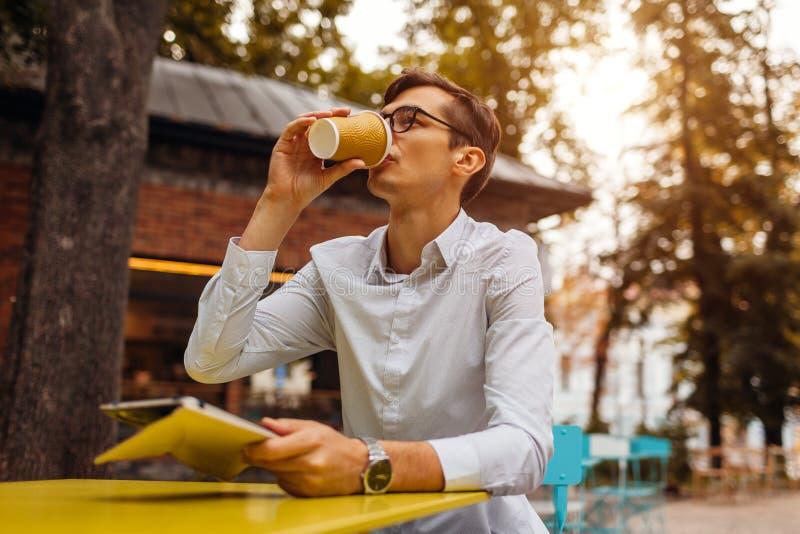 Il giovane uomo d'affari gode del caffè in caffè all'aperto facendo uso della compressa Tè bevente del tipo bello sulla via della fotografia stock