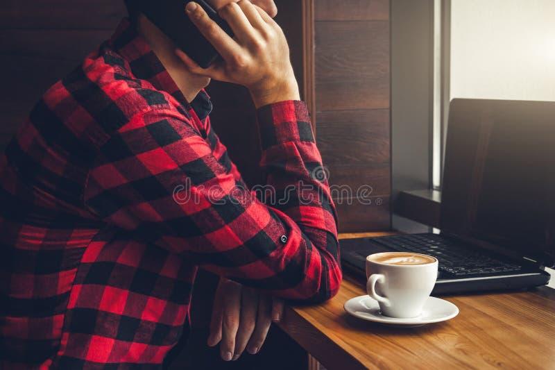 Il giovane uomo d'affari gode del caffè nel caffè che parla sul telefono e che per mezzo di un computer portatile immagine stock libera da diritti