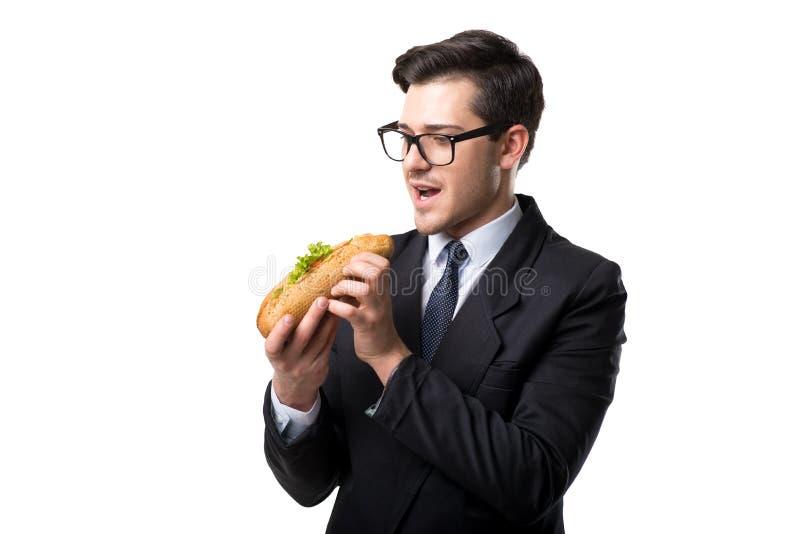 Il giovane uomo d'affari mangia l'hamburger, fondo bianco immagine stock