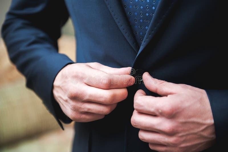 Il giovane uomo d'affari mette un vestito sopra prima della riunione dei partner fotografia stock