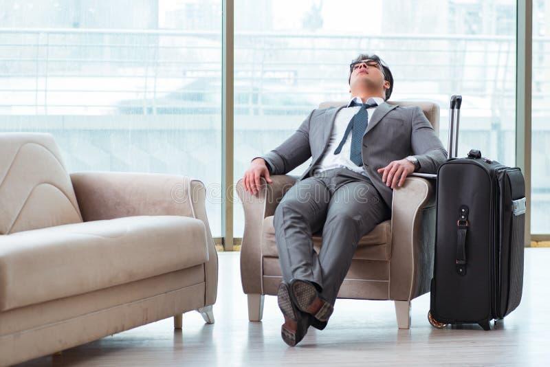 Il giovane uomo d'affari nel volo aspettante del salotto di affari dell'aeroporto immagini stock libere da diritti