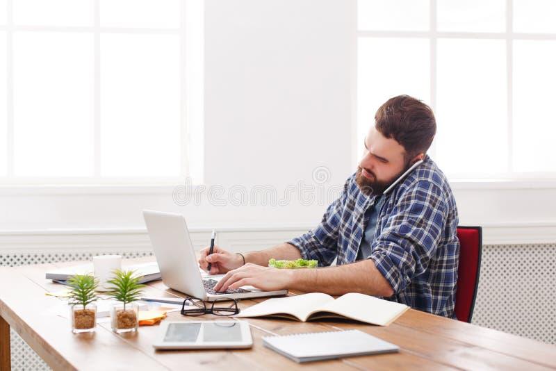 Il giovane uomo d'affari occupato con il computer portatile pranza in ufficio bianco moderno immagine stock