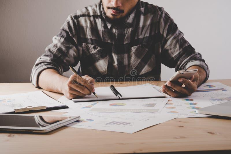Il giovane uomo d'affari scrive in un taccuino mentre lavora i Bu dell'analisi fotografie stock