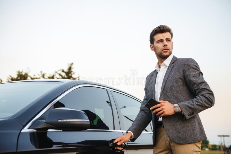 Il giovane uomo d'affari sicuro in vestito apre la sua automobile immagini stock libere da diritti