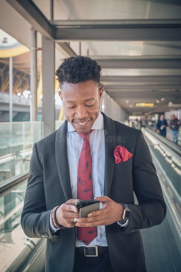 Il giovane uomo d'affari sta su fuori dell'aeroporto che esamina il Th fotografia stock